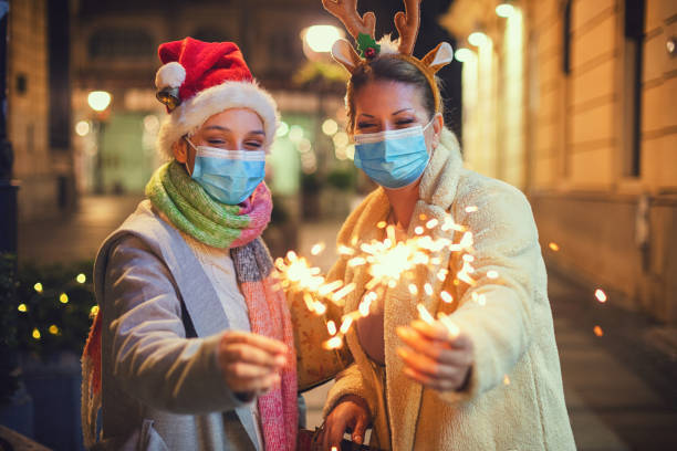 Young family having fun while celebrating Christmas in the city. They wears a protective mask to protect from corona virus COVID-19.